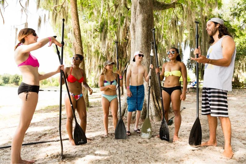 Students holding paddles by Lake Virginia.