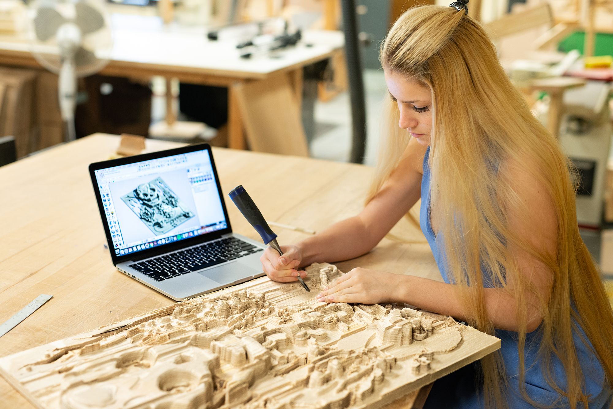 A student cleaning up her topographical CNC wood cutting with a small chisel.