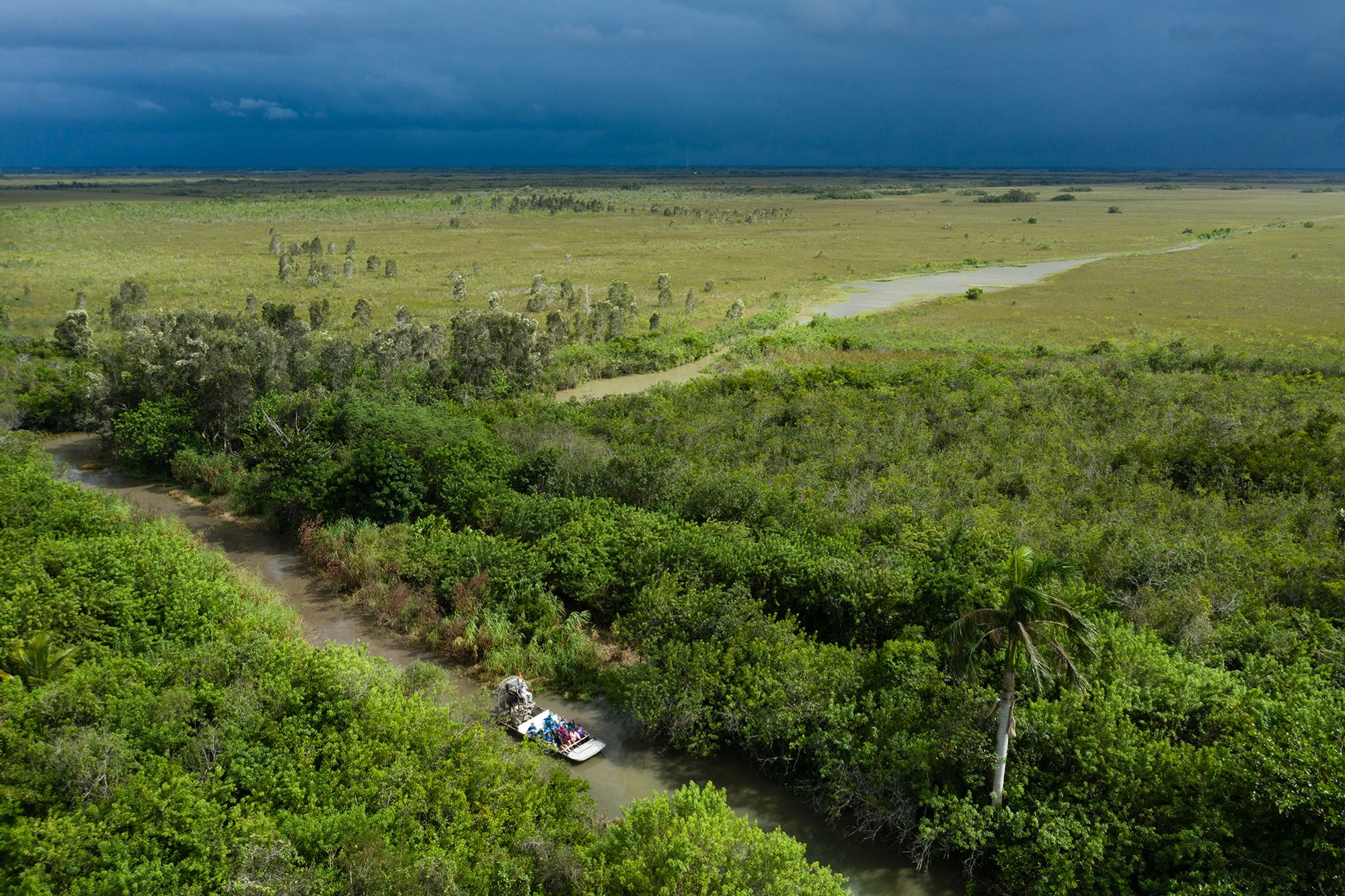 An aerial photo of an airboat driving through a canal with a storm on the horizon.
