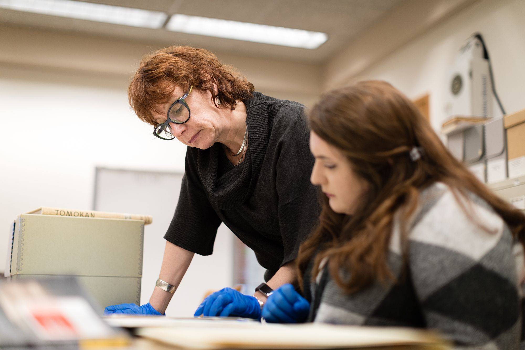 Claire Strom looking at research documents with a student while wearing protective gloves.