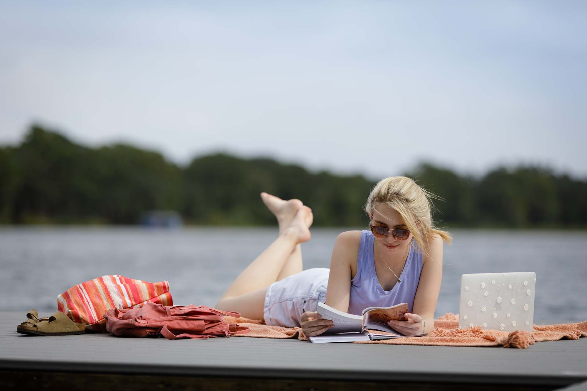 A student reads a book at the Rollins dock