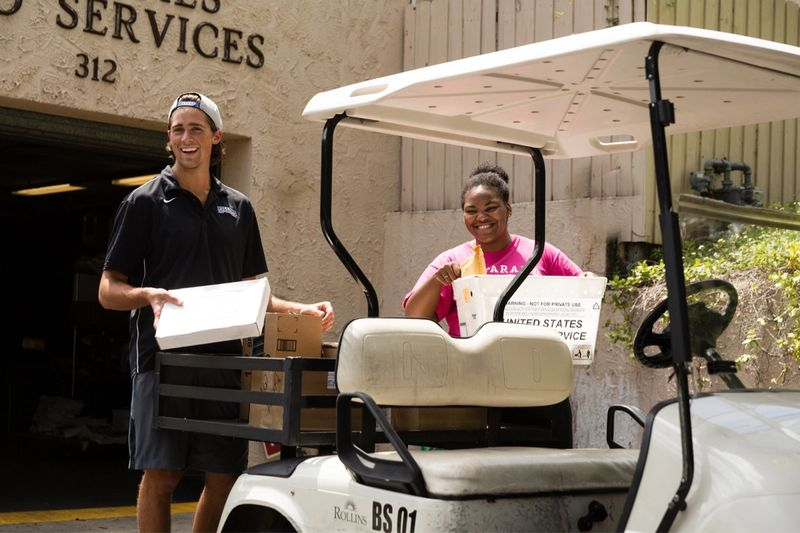A work study student helps deliver mail.