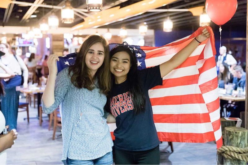 Two students hold an American flag.