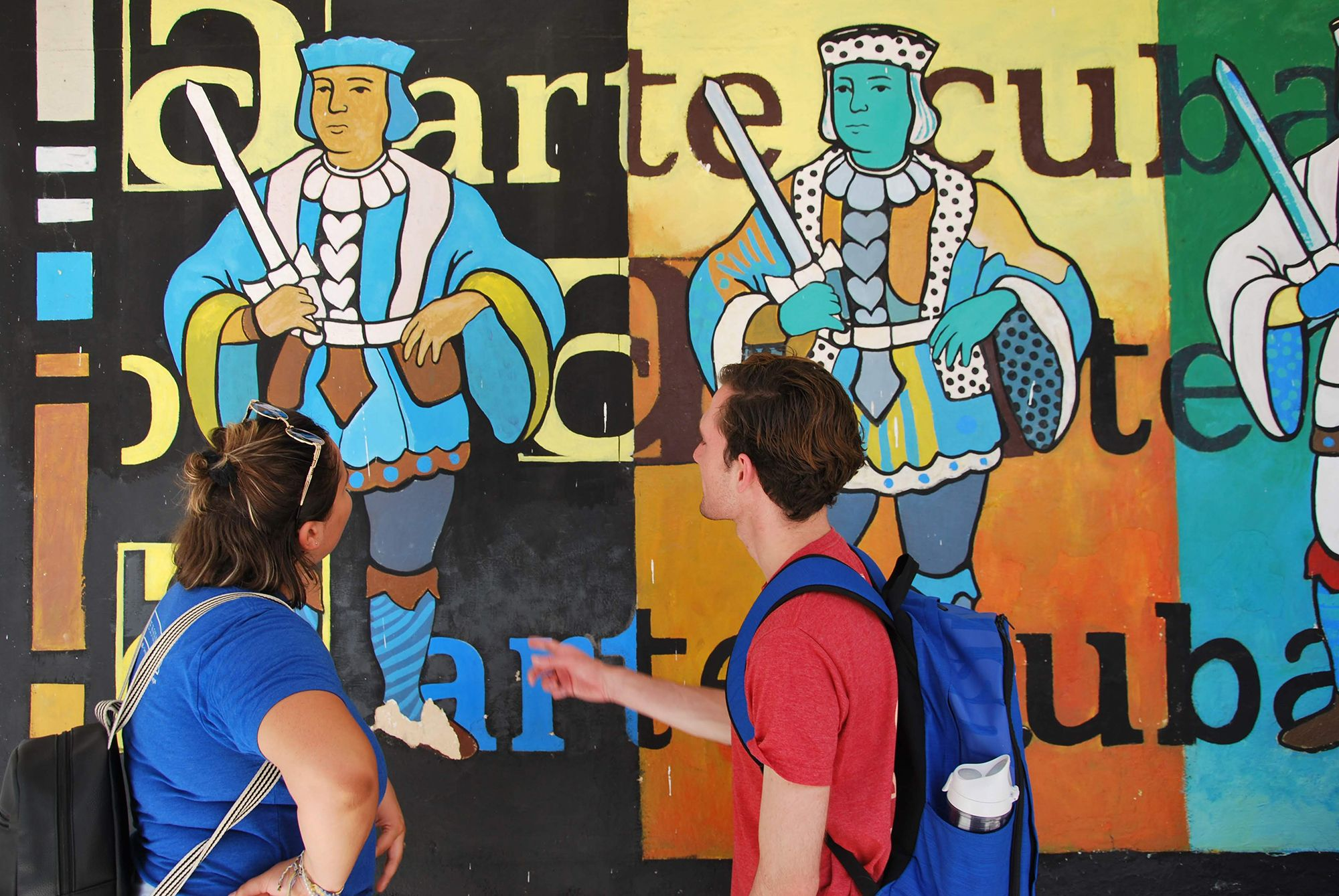Rollins students discuss an art mural on a field study to Cuba.