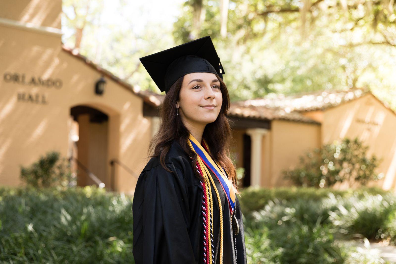 Karina Barbesino '19 dressed in graduation regalia on campus.
