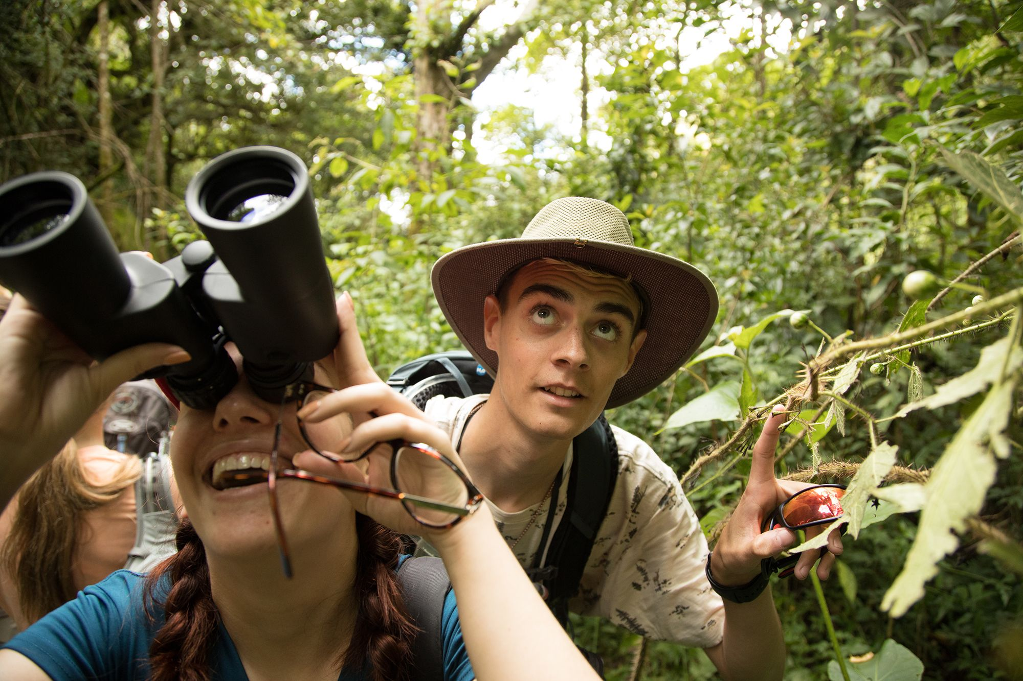 Students using binoculars to spy flora and fauna in a Costa Rican rainforest.