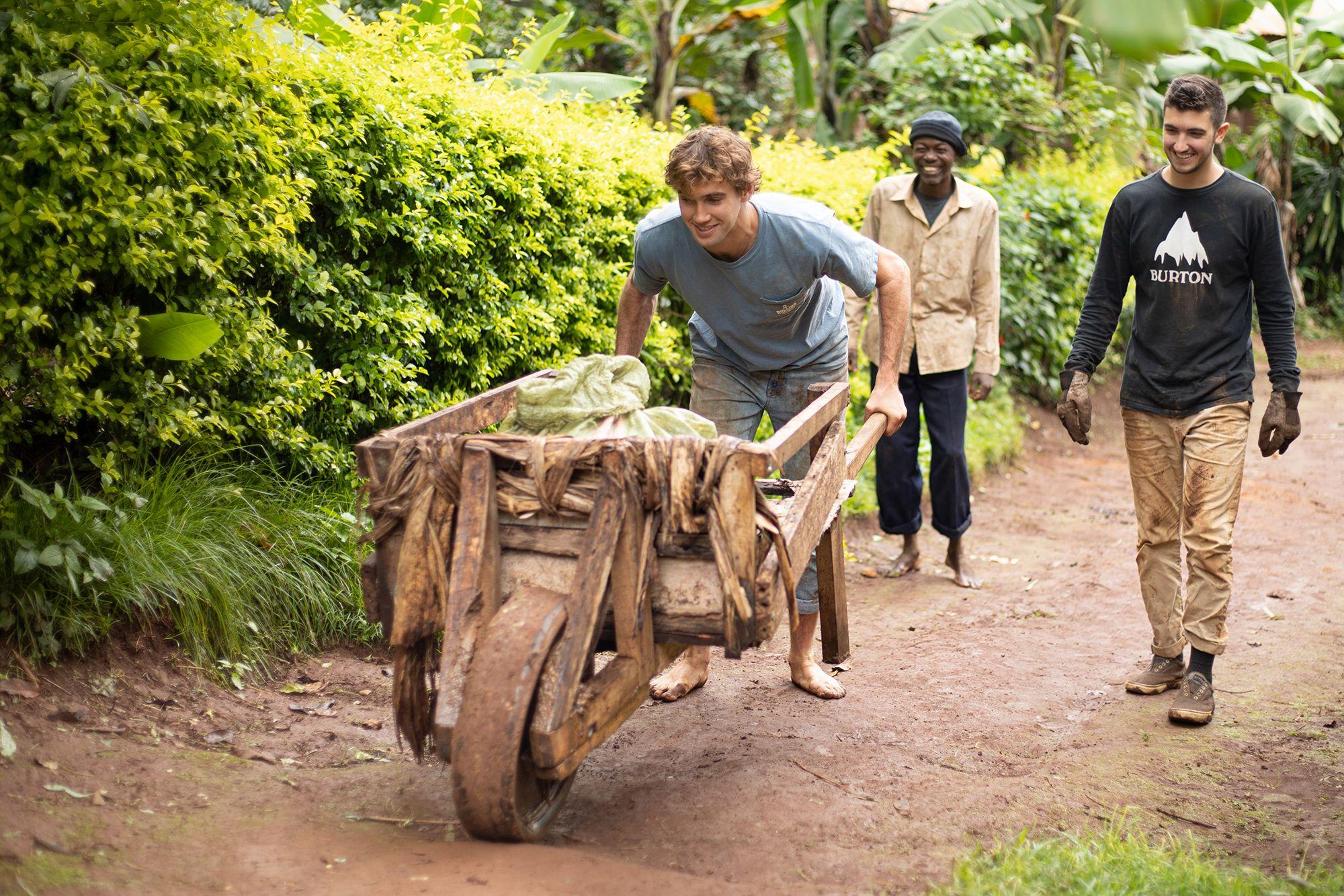 A college student pushing a wooden wheelbarrow barefoot along a dirt path.