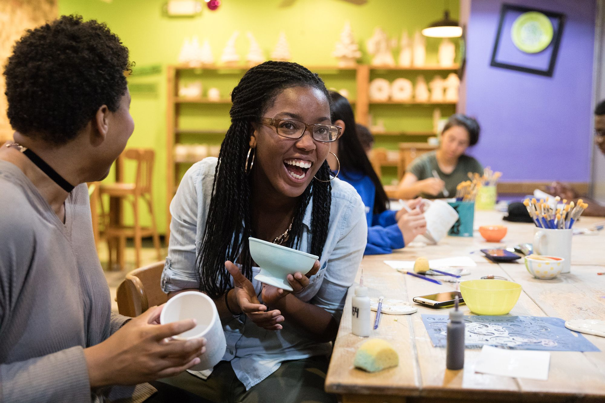 A student laughs with a classmate at a coffee shop.
