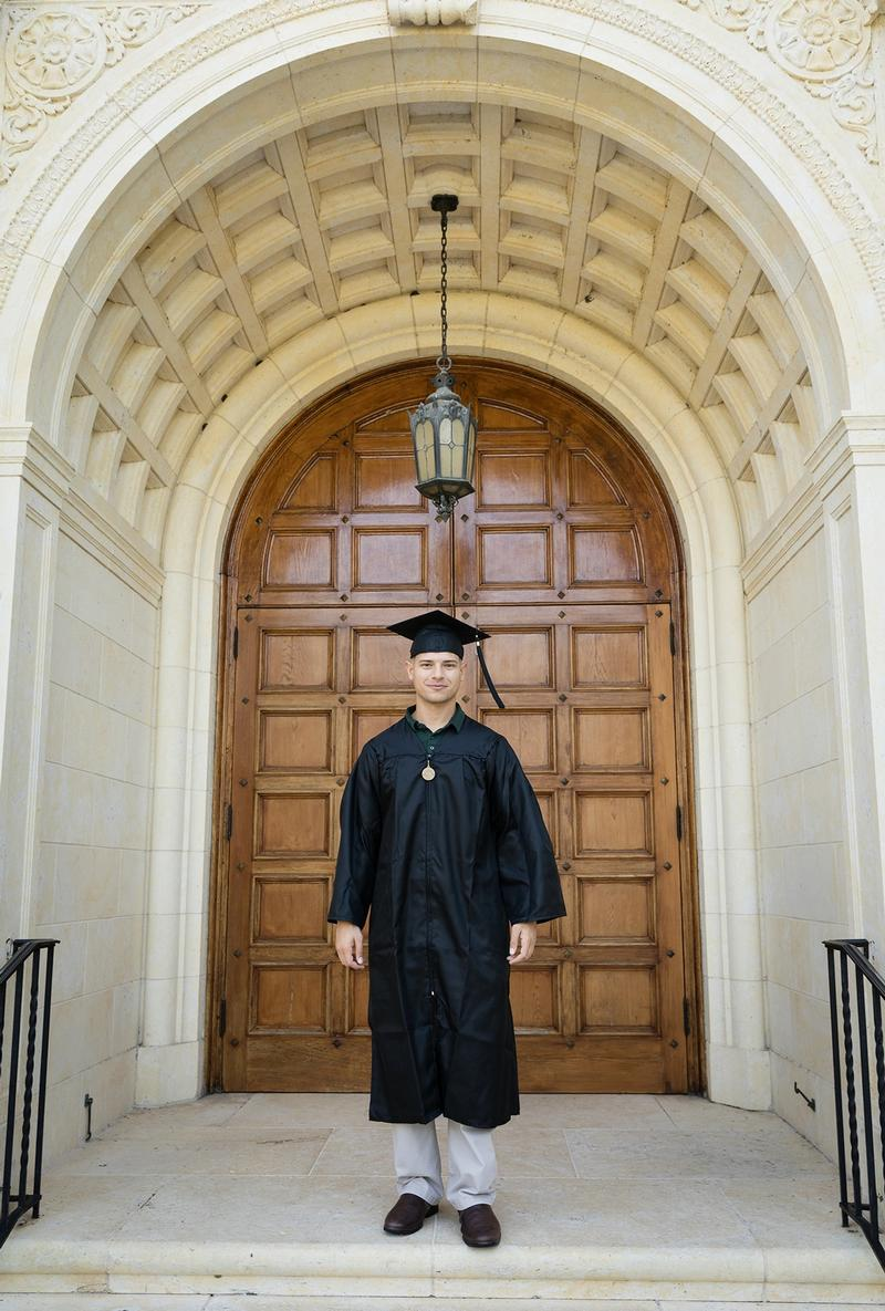 A college graduate poses in cap and gown in front of Rollins' Knowles Memorial Chapel.