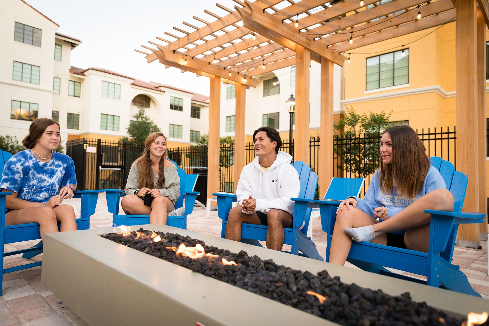 A group of students hang out by an outdoor firepit.