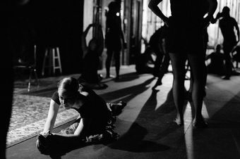 A student dancer stretches before class.