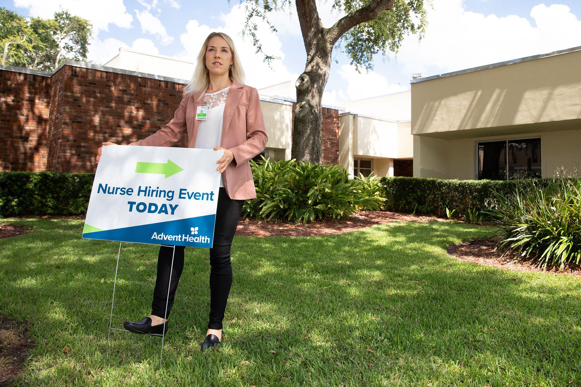 As part of her internship, Nina Steigerwald '20 sets up signs to promote AdventHealth's employee wellness program.