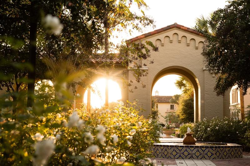 Sunlight spills through a campus archway illuminating a fountain and the rose garden.