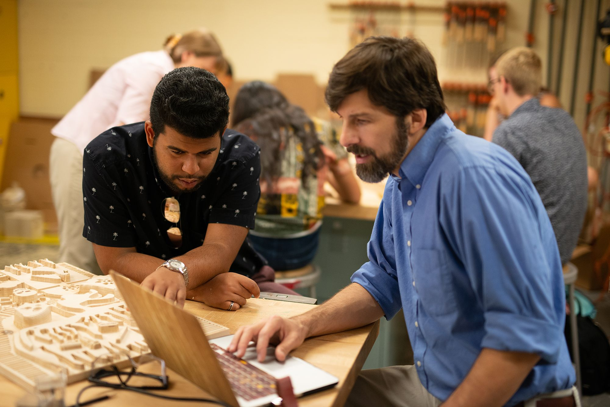 Art professor and student compare a relief to their computer models.