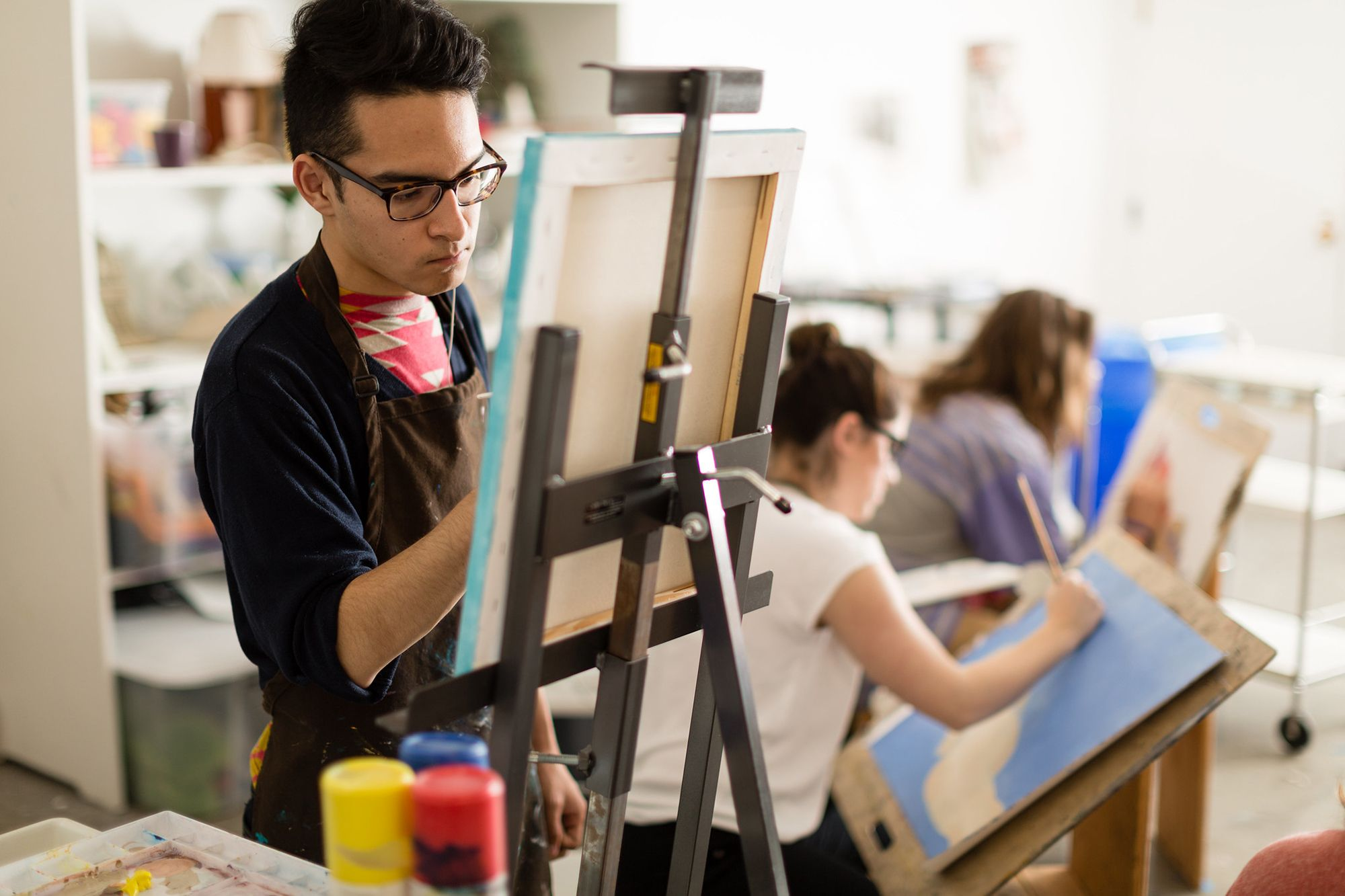 A studio art college student painting during class.