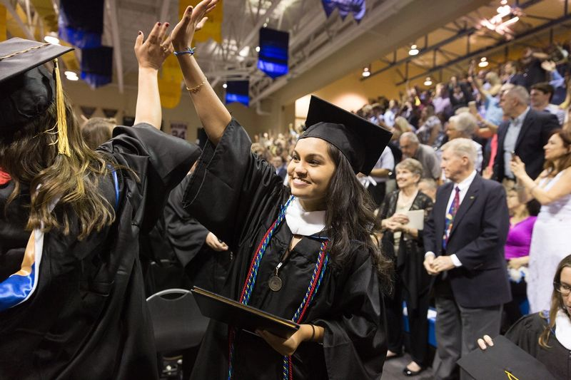 A graduate waves to her family in the crowd during commencement.