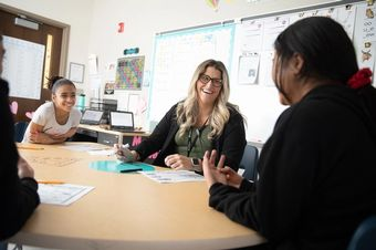 A teacher works with middle-school students.