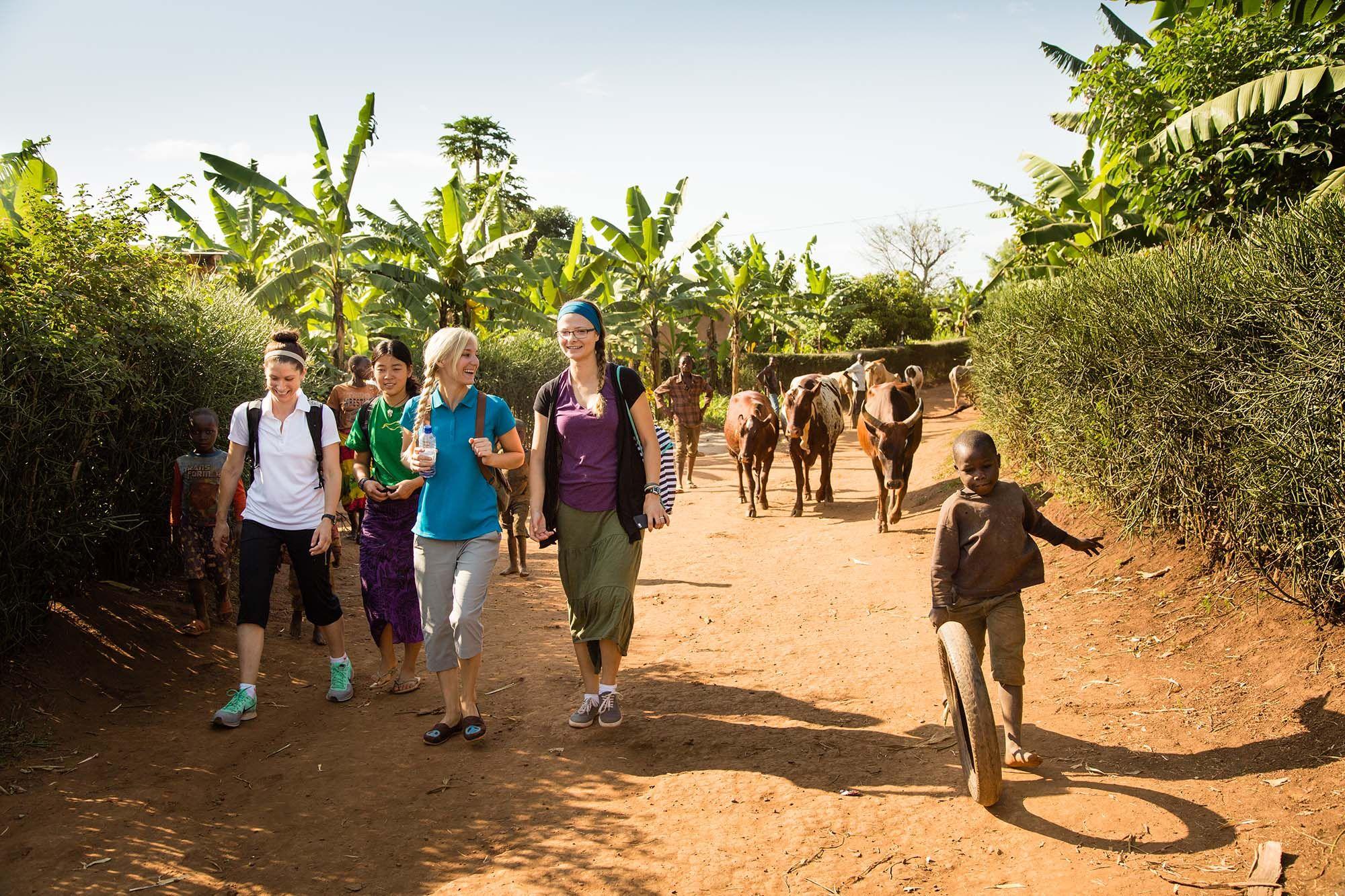 Students hike through a village in Rwanda on a field study.