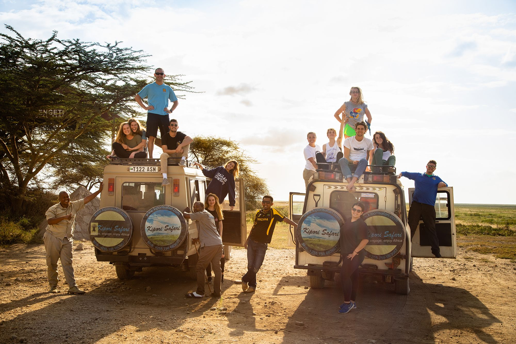 Students pose on top of jeeps during a safari in Serengeti National Park.