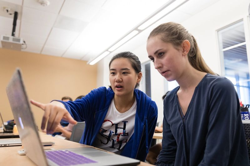 Two students collaborate on a class project.