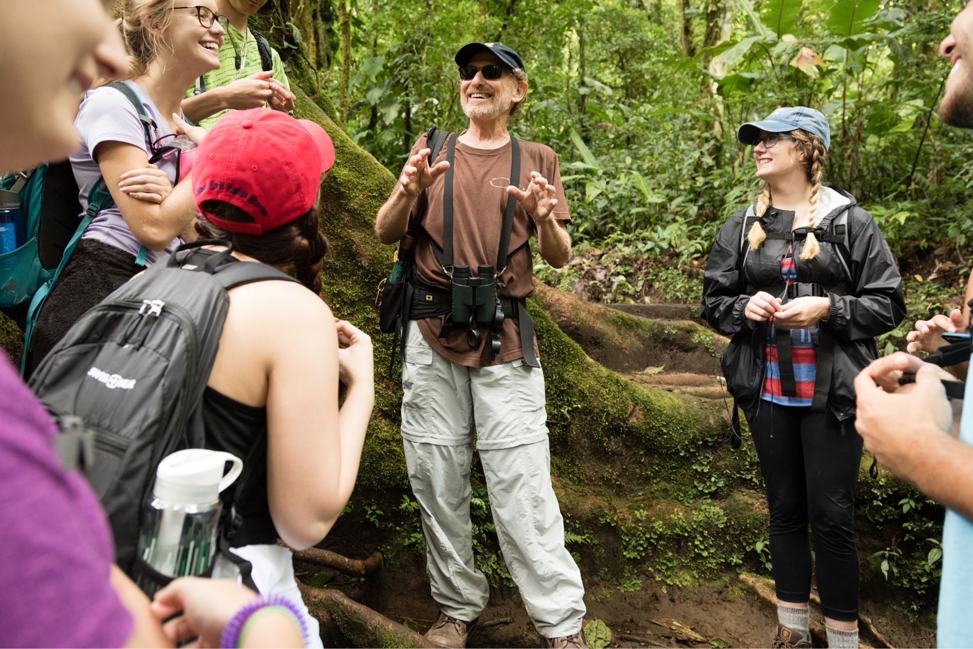 Ecology college professor addressing his class as they stand near a large tree in a Costa Rican rain forest.