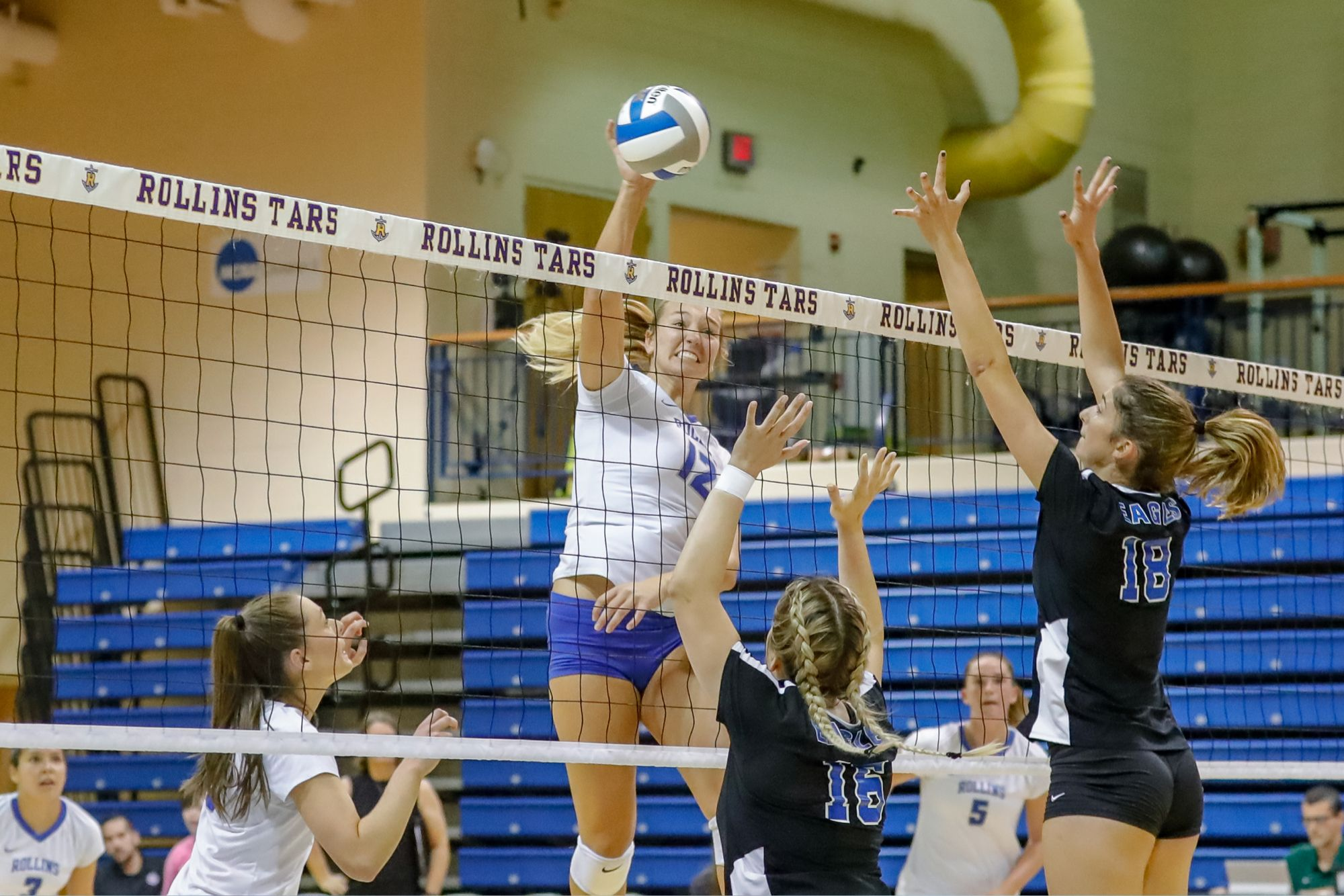 A middle hitter on the volleyball team hitting at the net.