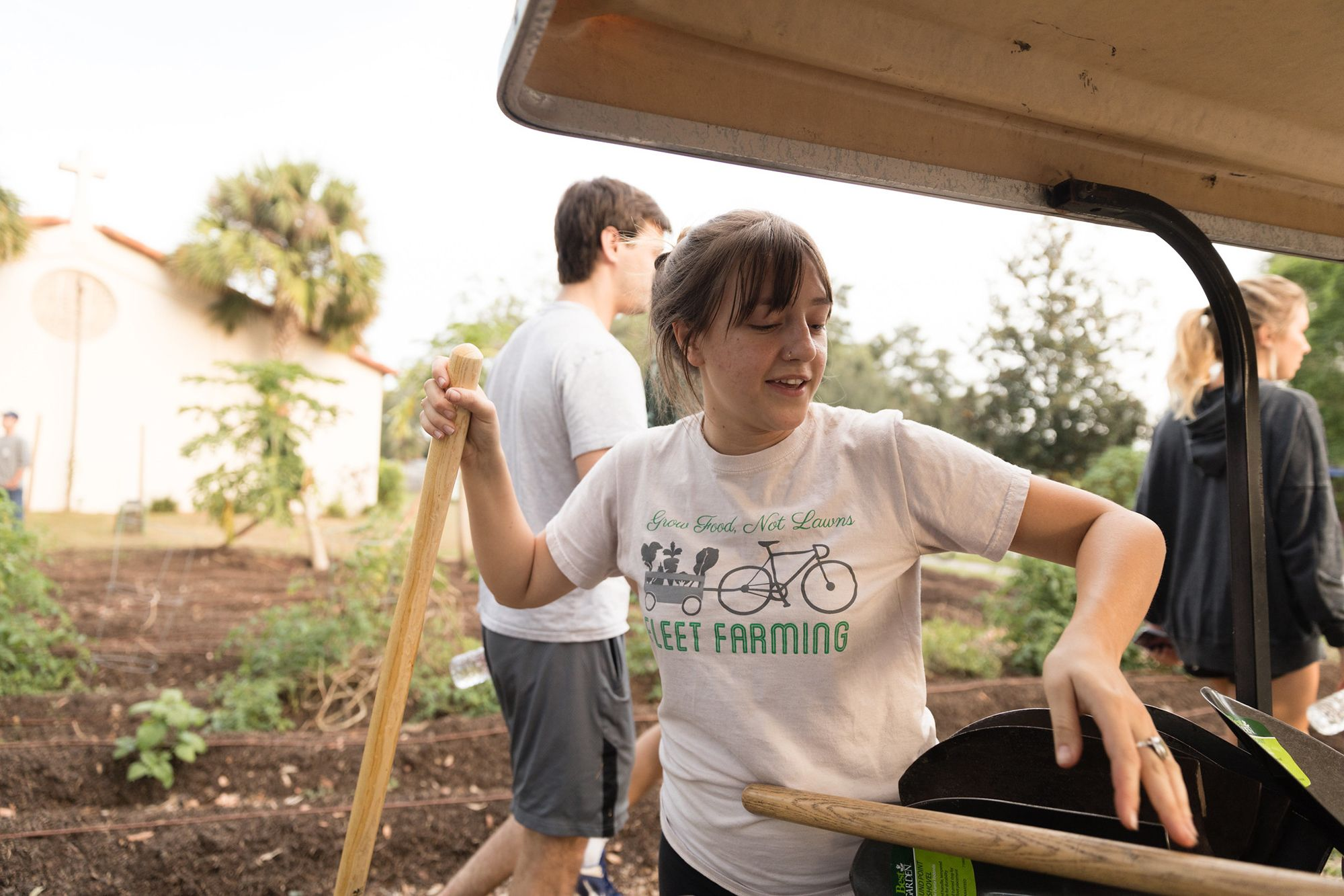 One of the Fleet Farming staff members grabbing supplies off the cart for planting.