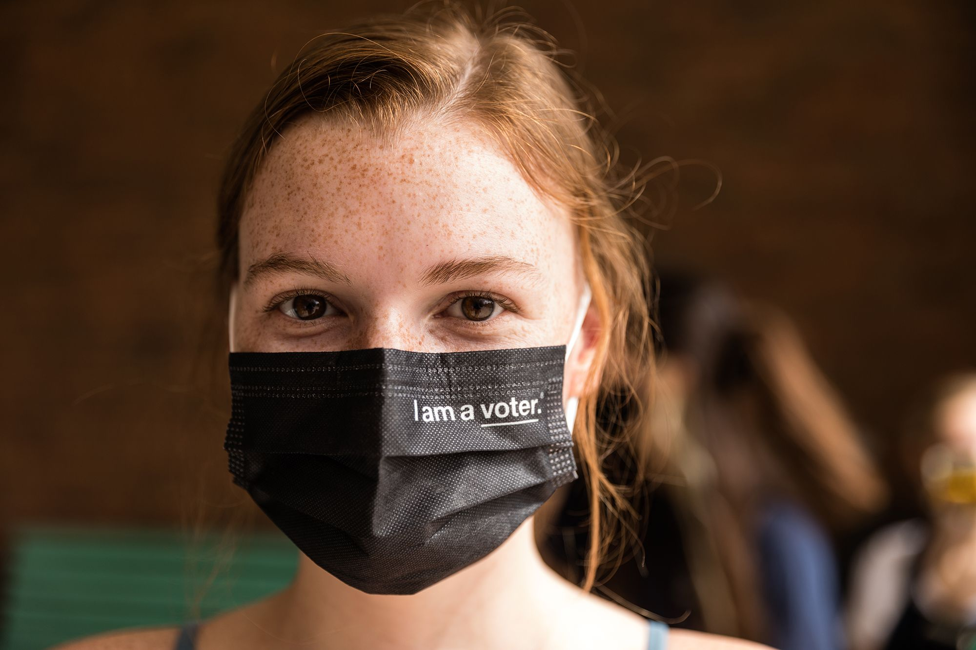 """A Rollins student wearing a black protective mask reading """"I am a voter."""""""