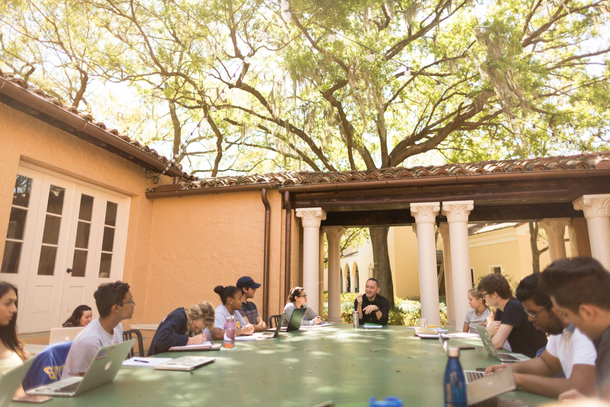 Rollins professor Dan Chong leads a discussion with students in the Orlando Hall outdoor classroom.