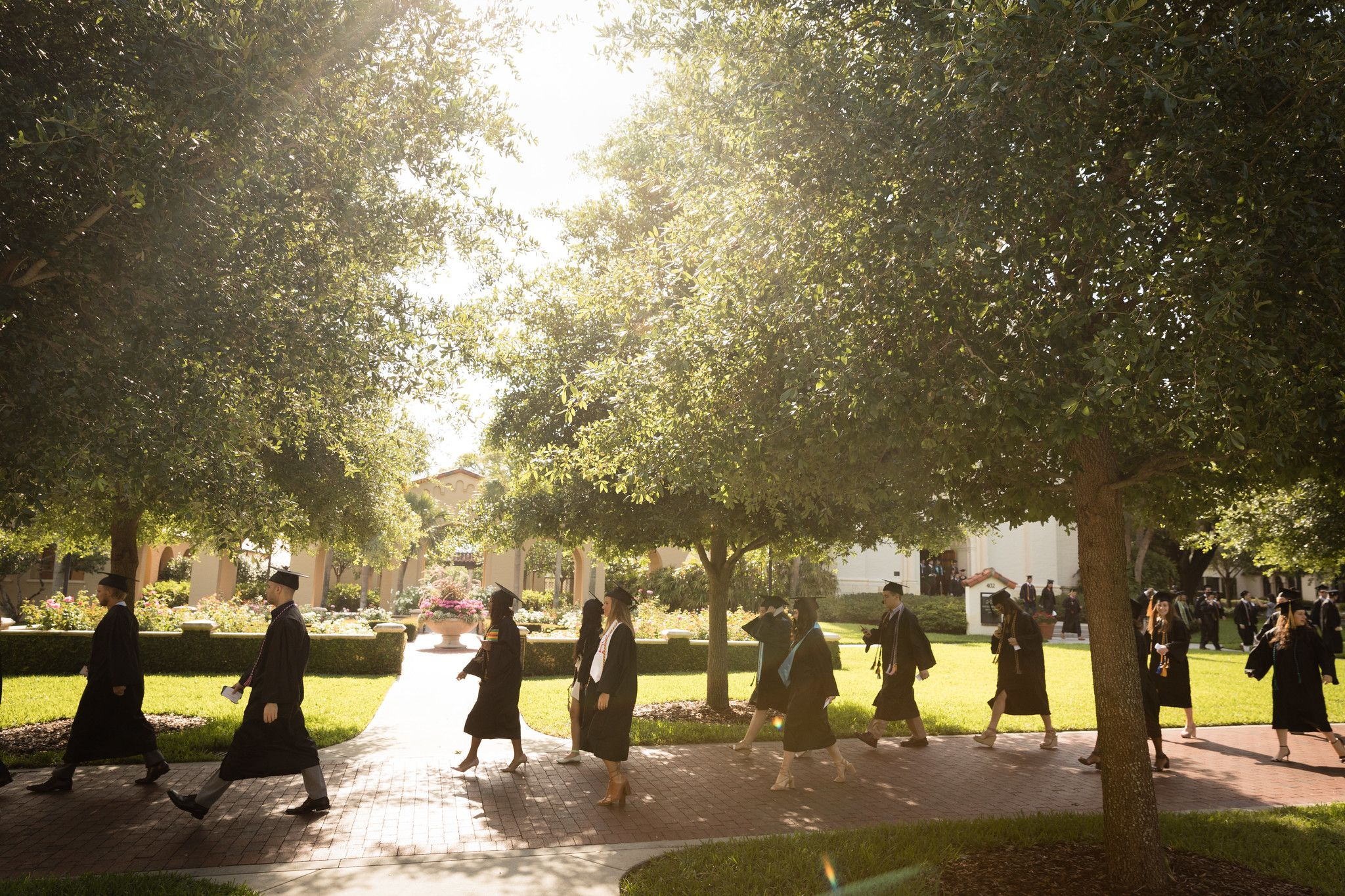 Students wearing caps and gowns walk to a commencement ceremony on Rollins College's campus.