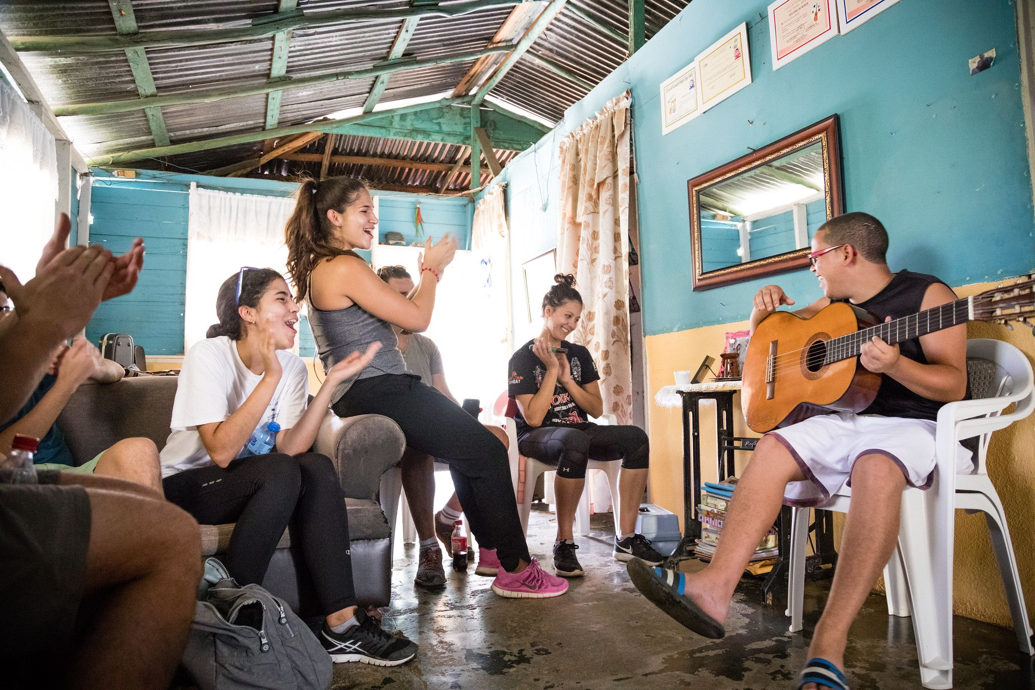Students join in the celebration as a local Dominican Republic boy plays the guitar. boy plays the guitar.