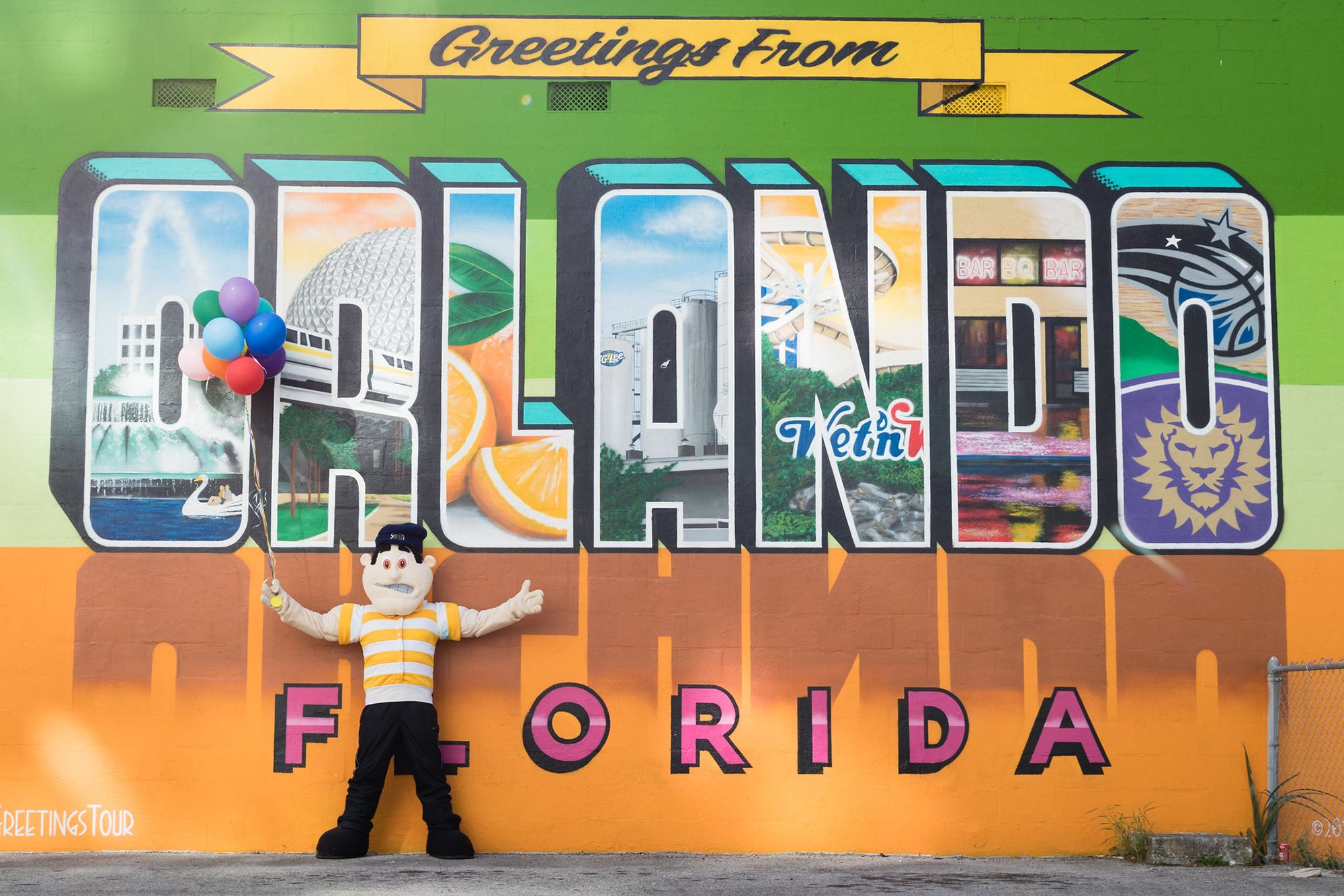 Tommy Tar posing with the Greetings from Orlando mural