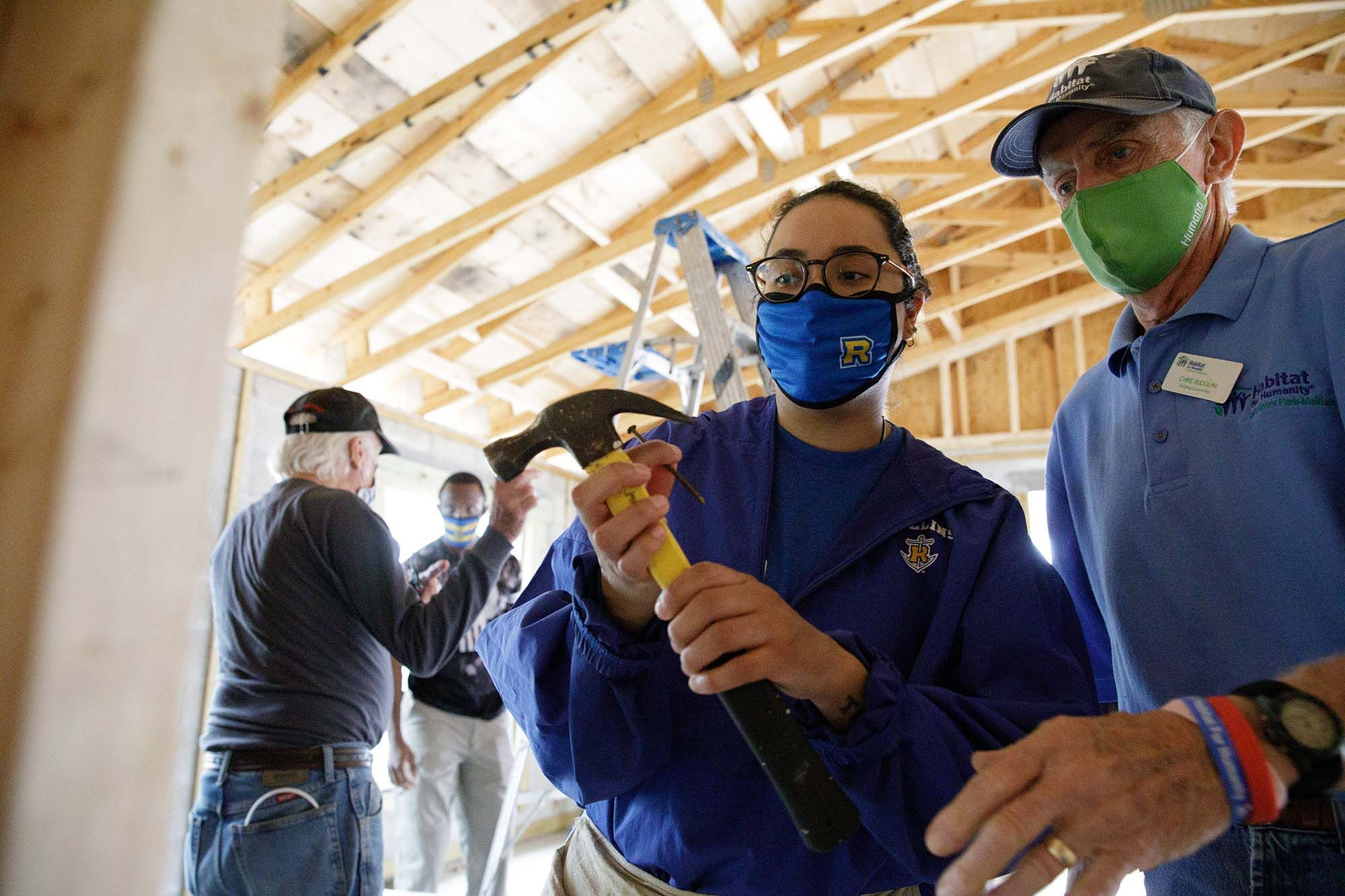 A student holds a hammer at Habitat for Humanity