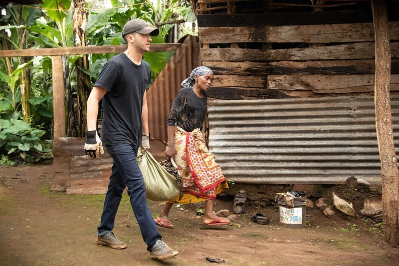Student and woman carrying leaves through village.