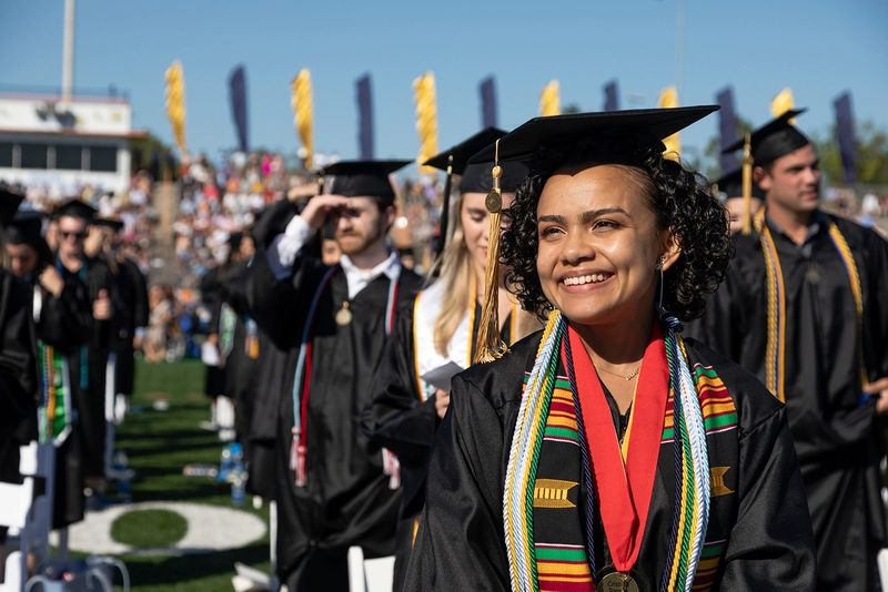 A students smiles during a commencement ceremony.
