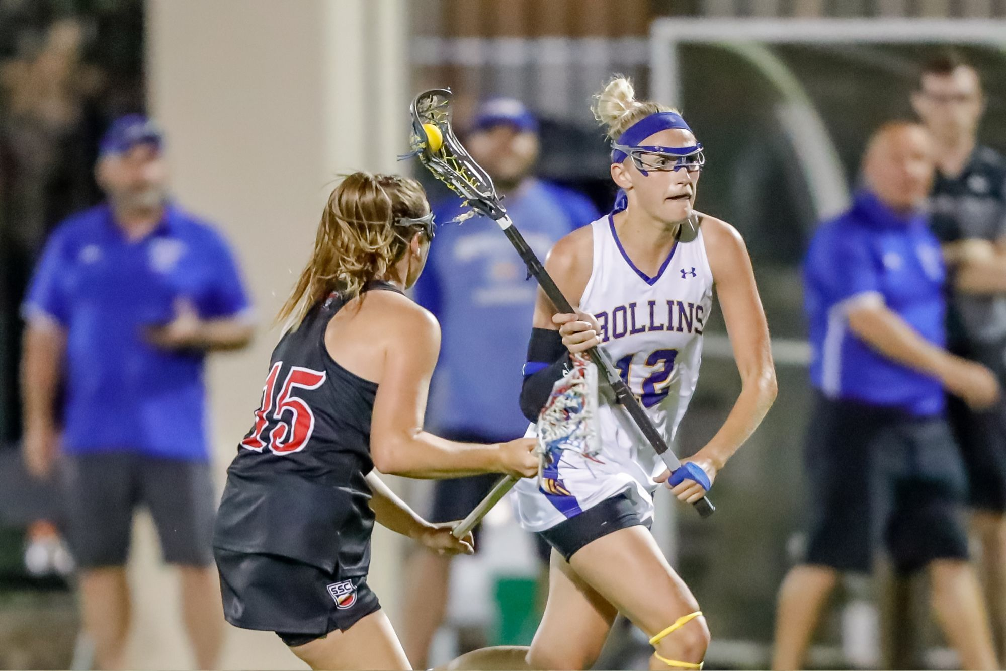A female lacrosse player running past a defender during a game.