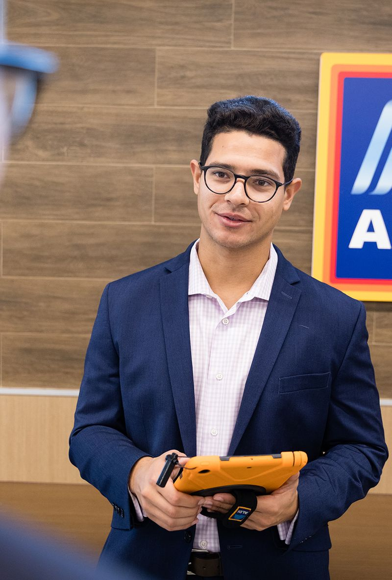 A student talks with his manager during an ALDI internship.