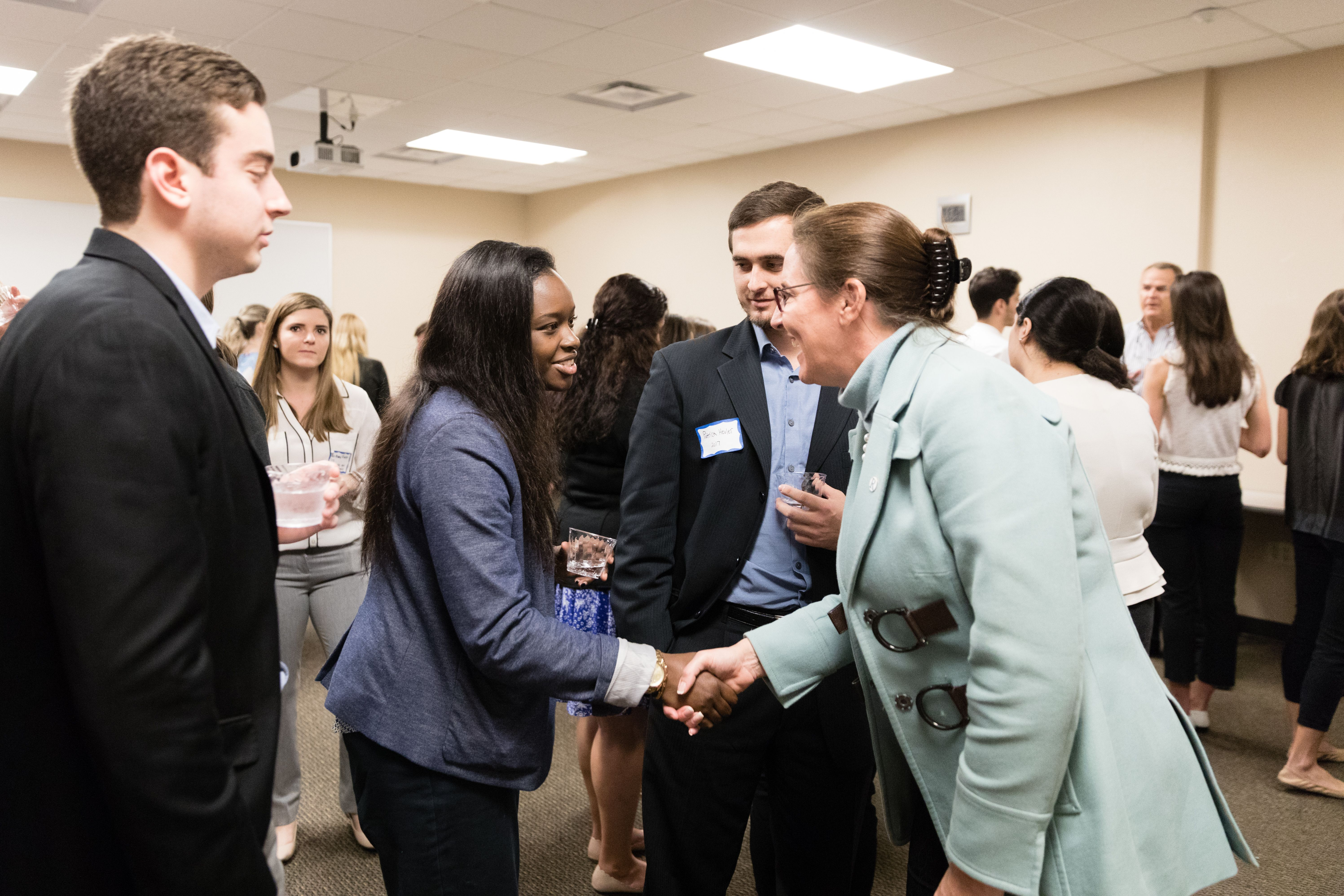 Students shake hands at a networking event.
