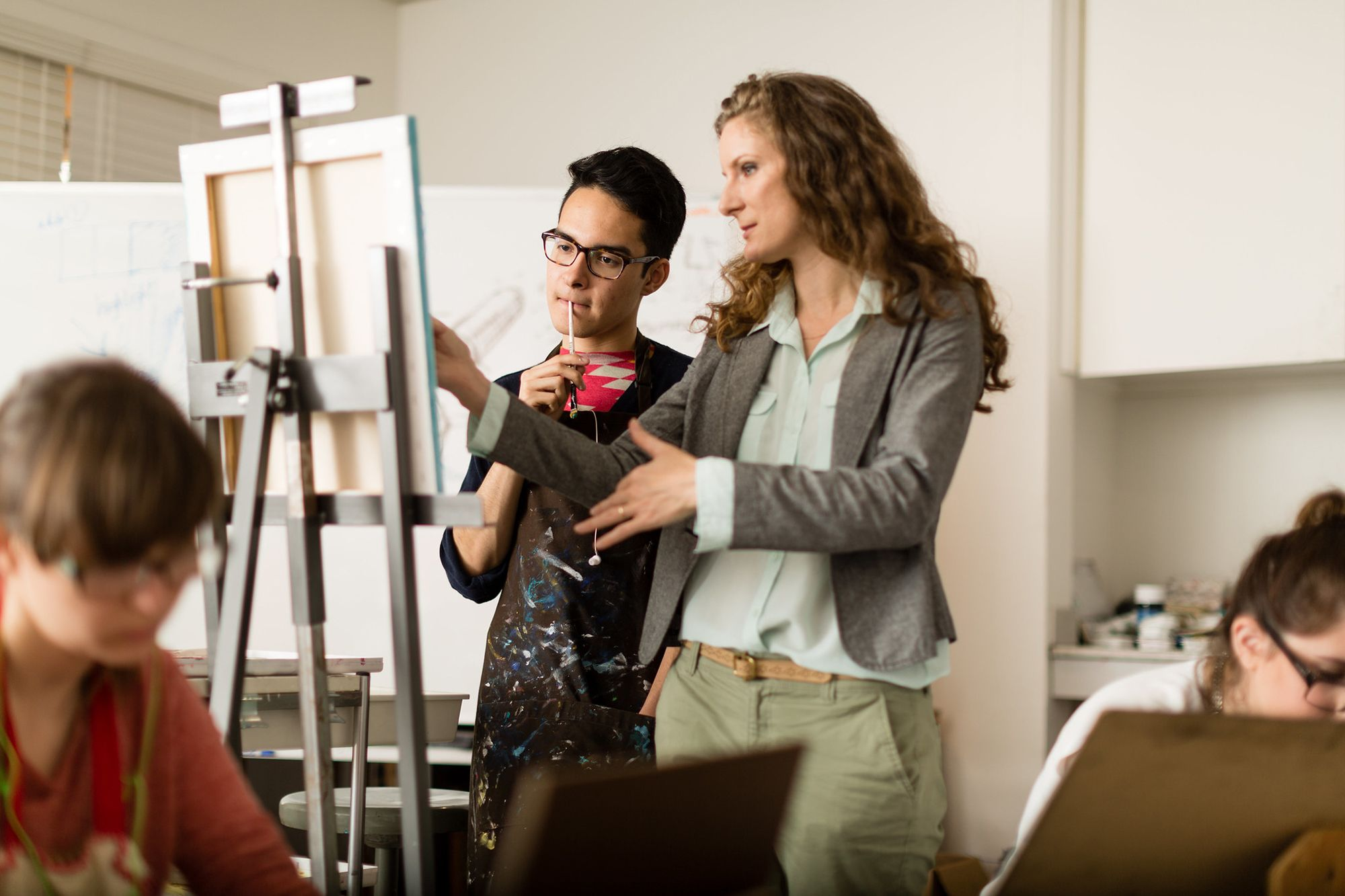 A studio art professor giving advice to her student as he paints his canvas resting on an easel.