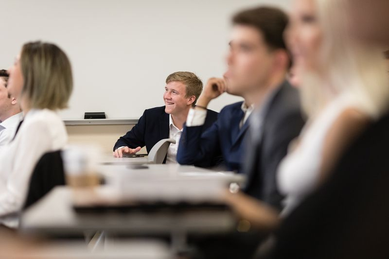 A student smiles during a business class at Rollins.