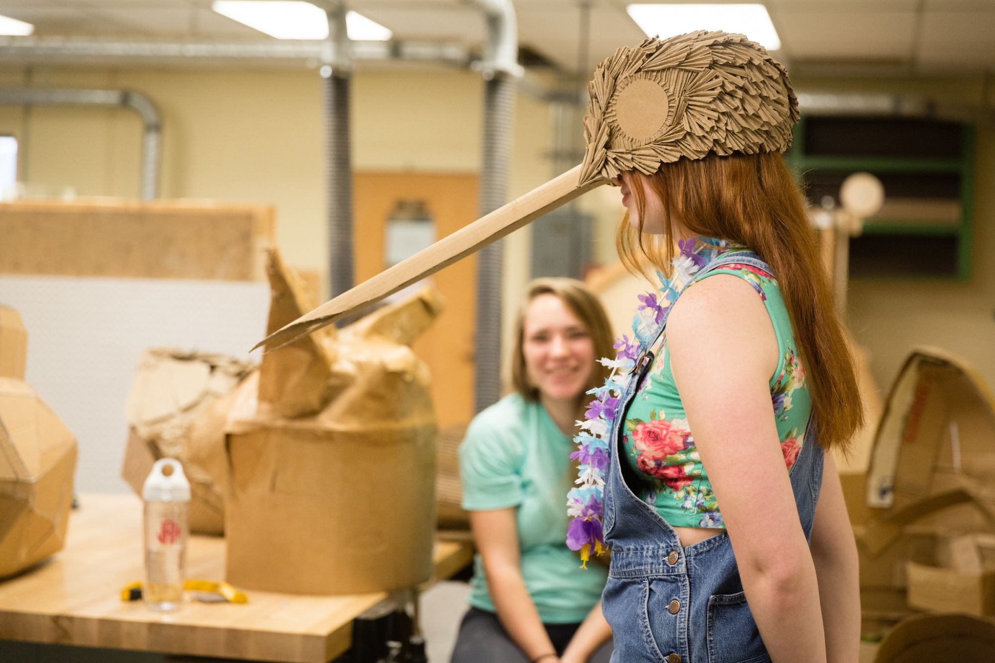 A student wearing a cardboard hummingbird hat that she made in her Foundations in Sculpture course.