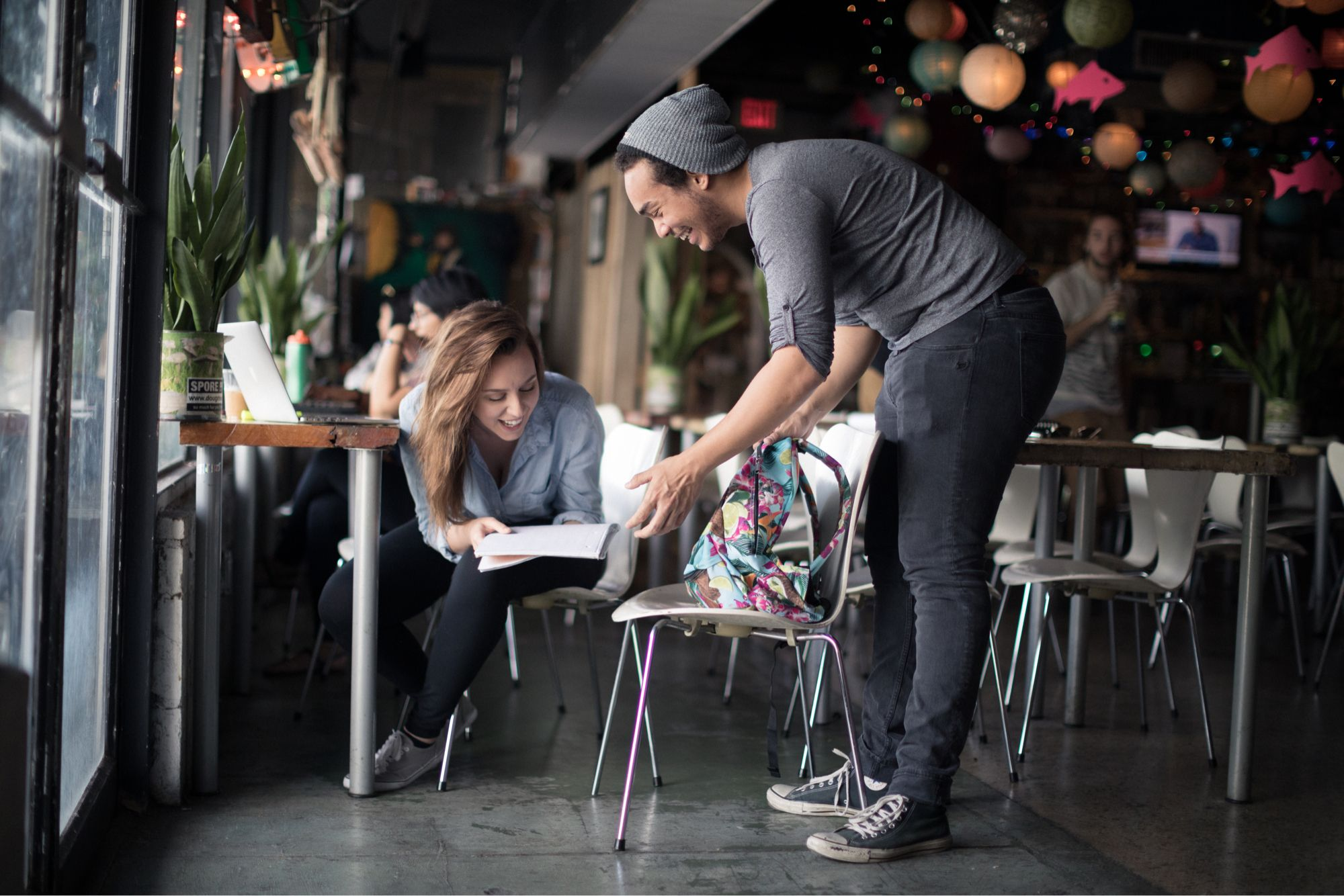 Two college students laughing at an assignment in a local coffee shop.