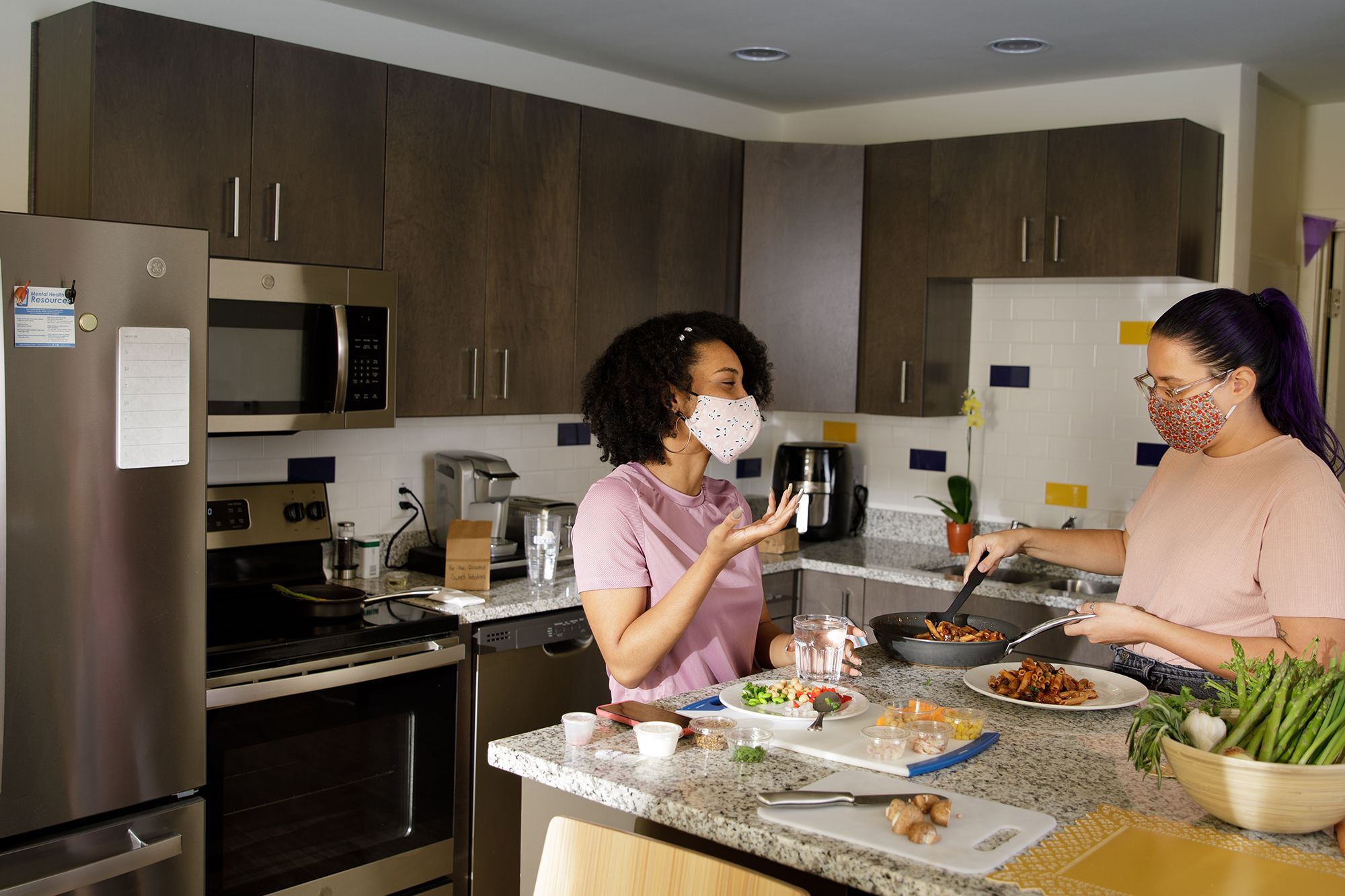 Masked student cook in their apartment kitchen