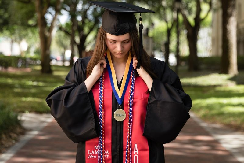 A college graduate poses in her cap and gown on the Rollins College campus.