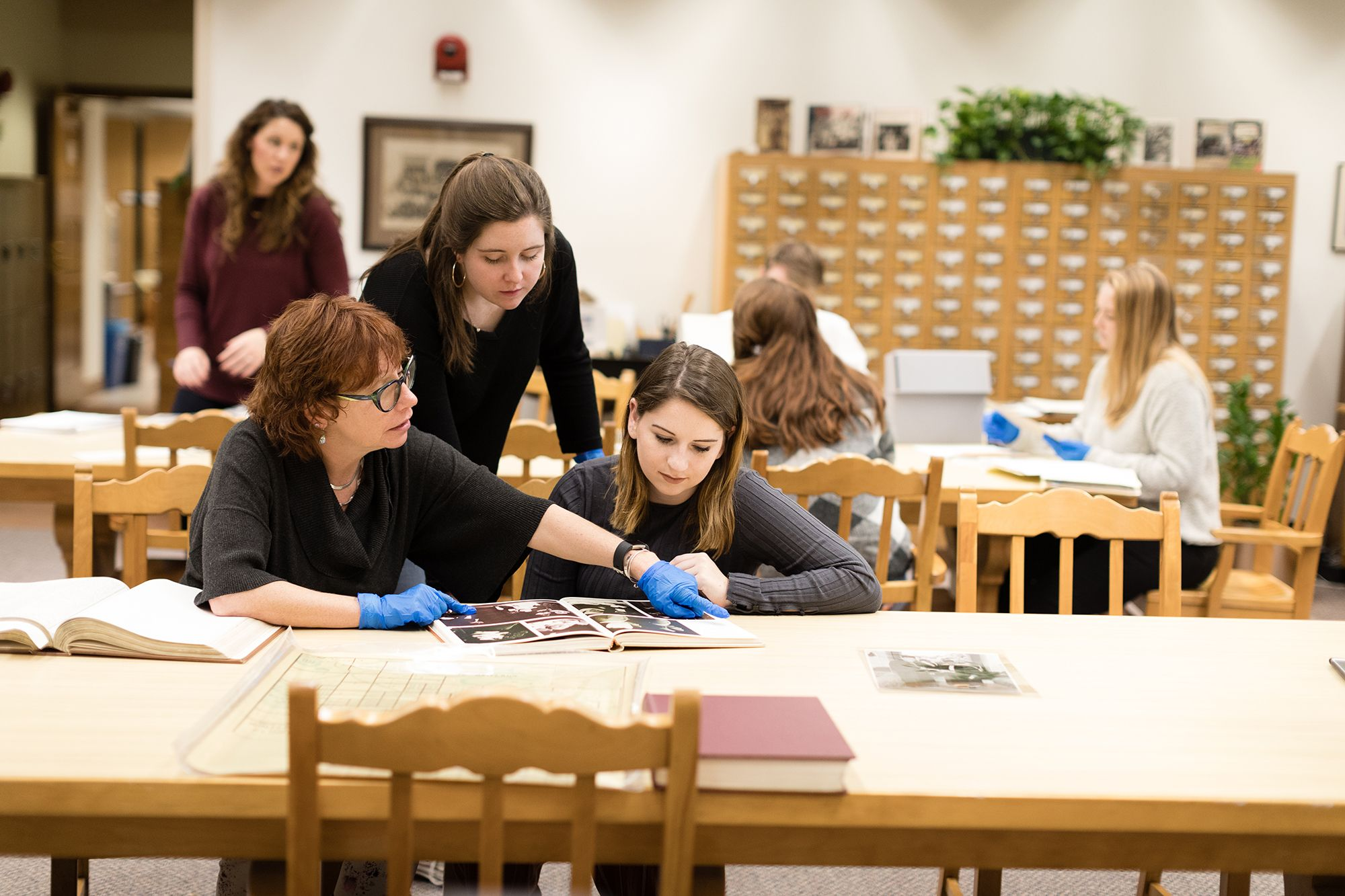 A professor works with a pair of students in the Rollins College archives.