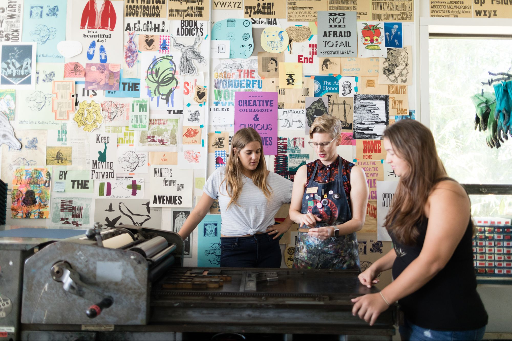 Art studio college students and mentor at a large screen printing press.