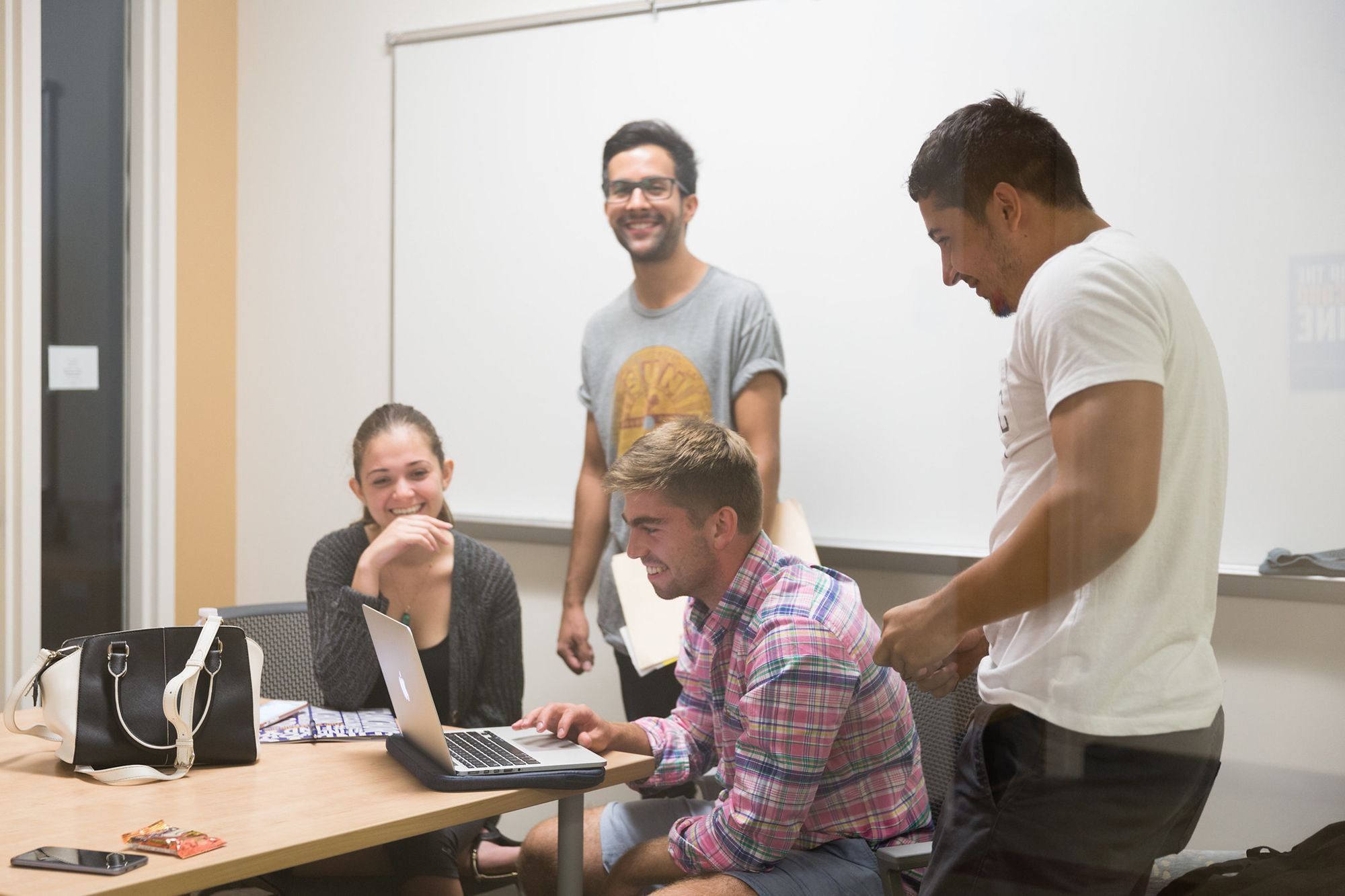 Students gathered around a friend on his computer laughing.