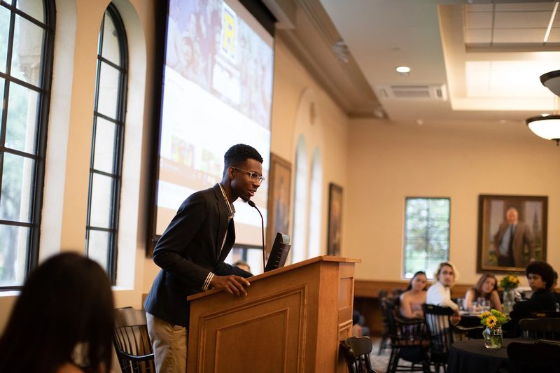A college student delivers a talk at a podium to a small crowd of campus visitors.