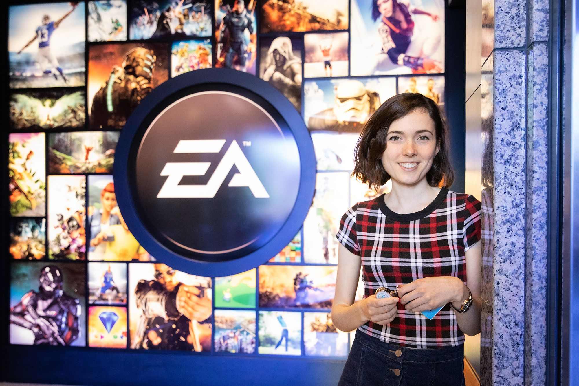 A Rollins grad poses in front of the EA logo at the company's Orlando headquarters.