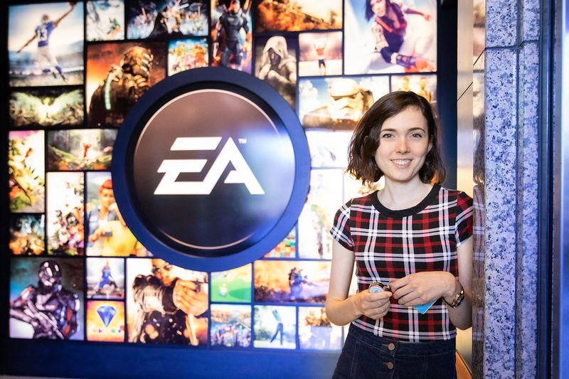 A software engineer poses in front of the EA Sports logo at the company's Orlando headquarters.